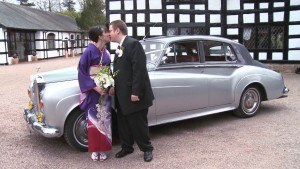 bride and groom outside Davenport Green Cheshire Hall with bride wearing Kimono and holding Orchids