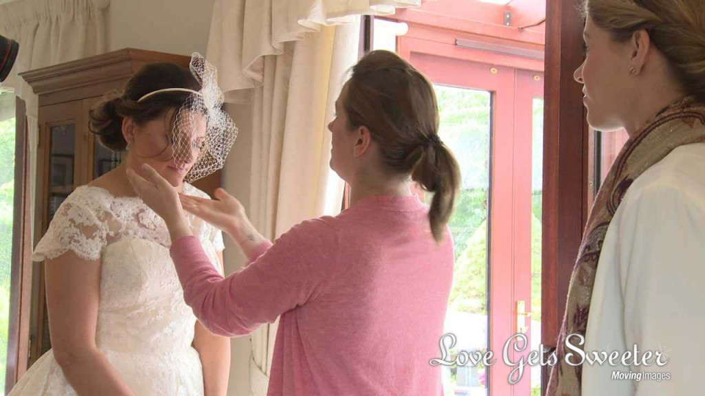 bride getting birdcage veil adjusted