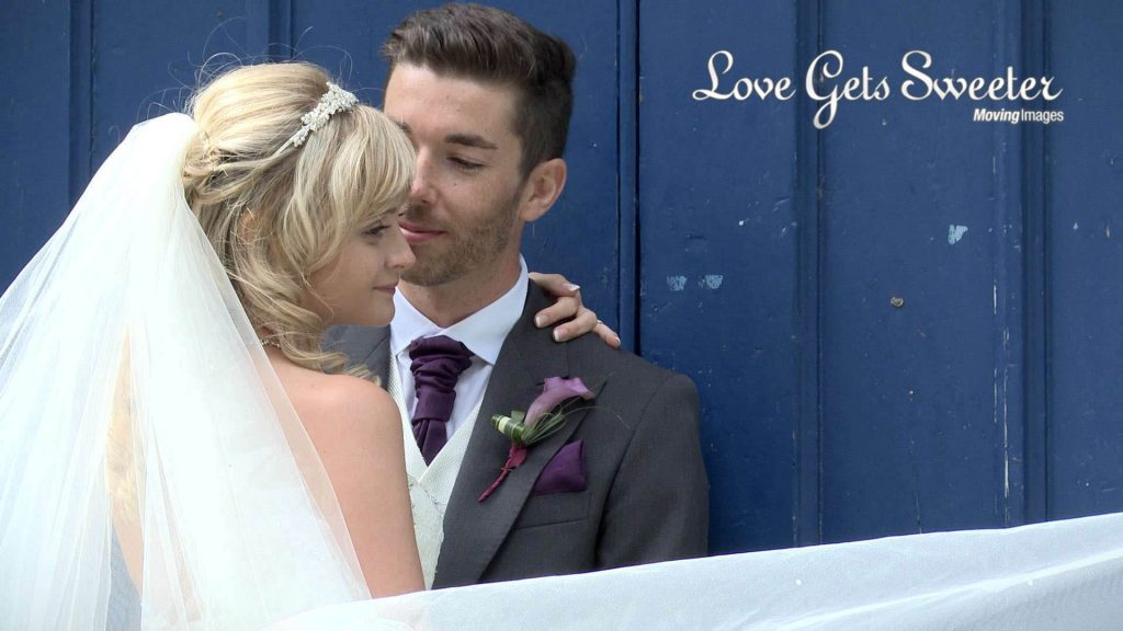 bride and groom outside a blue door for photos and video in sandbach