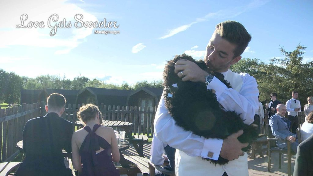 groom cuddling dog at wedding in sandbach cheshire