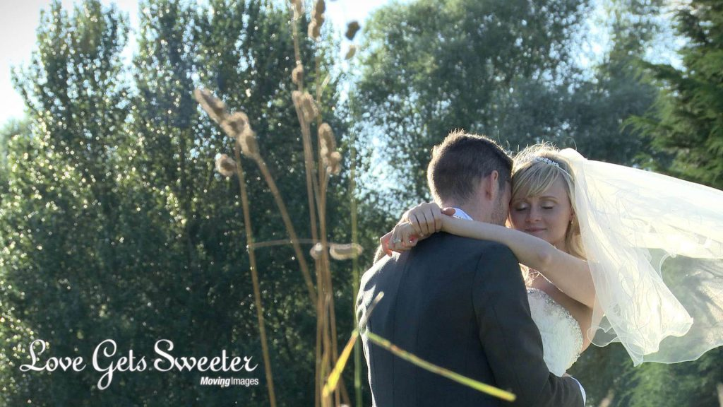 bride and groom having photos in the long grass at Malkins Bank Golf Club wedding