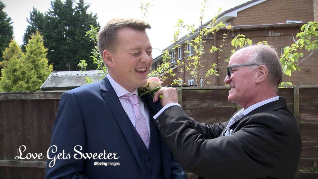 groom having buttonhole put on before liverpool wedding