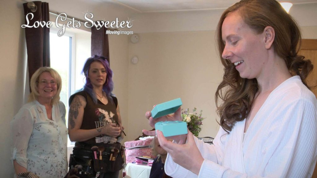 bride opening Tiffany gift off groom morning of her wedding