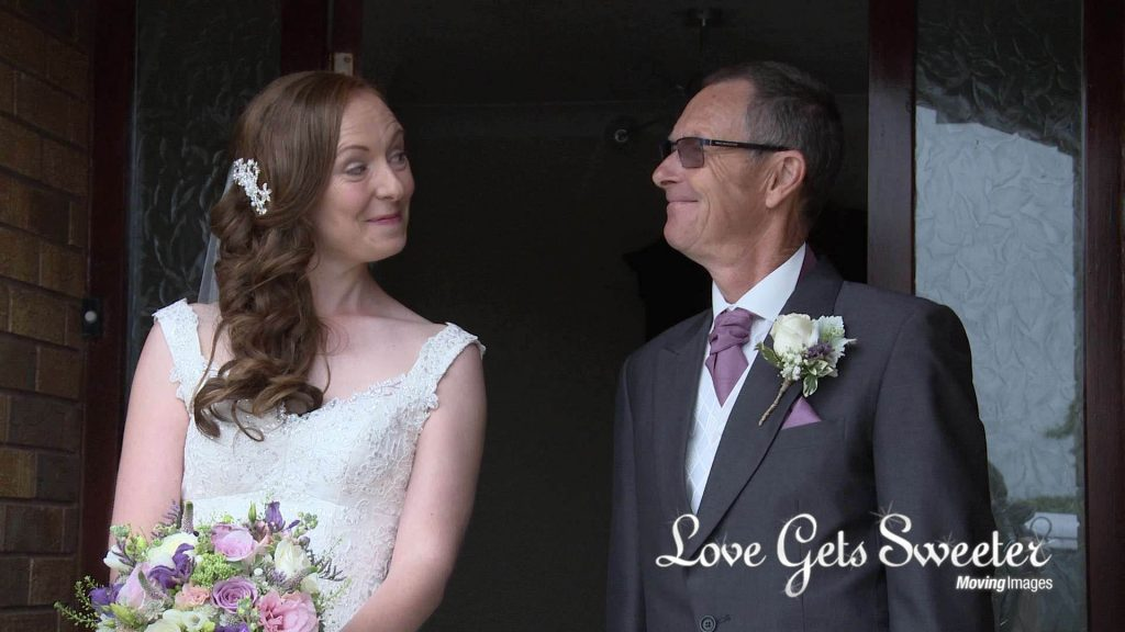 dad and daughter share a cheeky grin and smile before the wedding