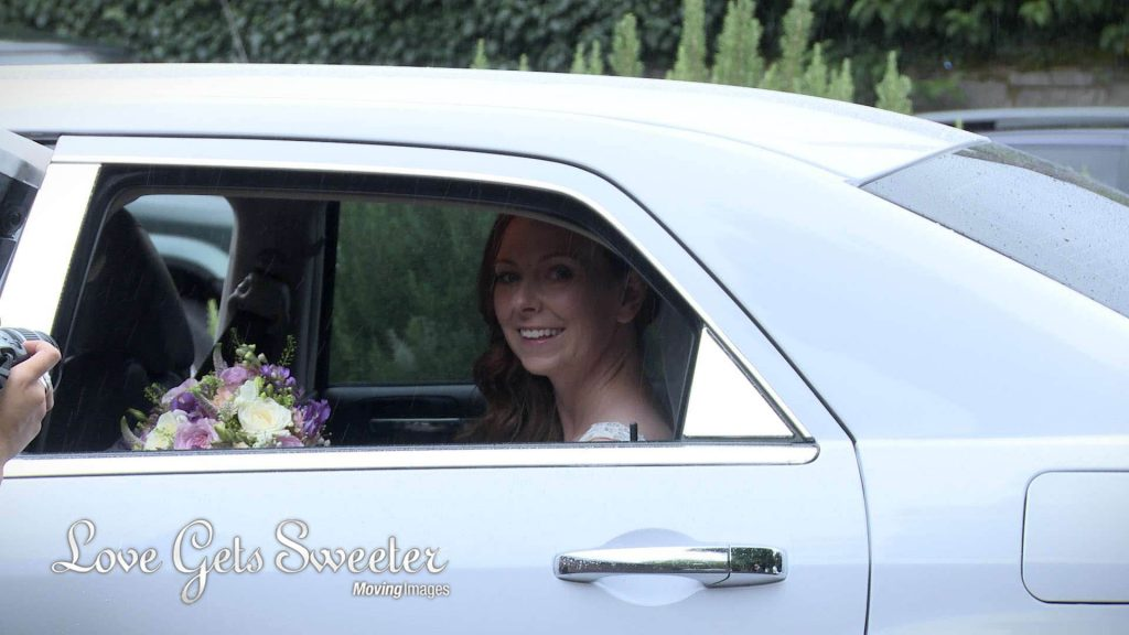 bride sat in her wedding car in the rain typical august wedding weather