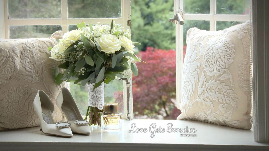 classic white bridal bouquet and shoes in Eaves Hall window