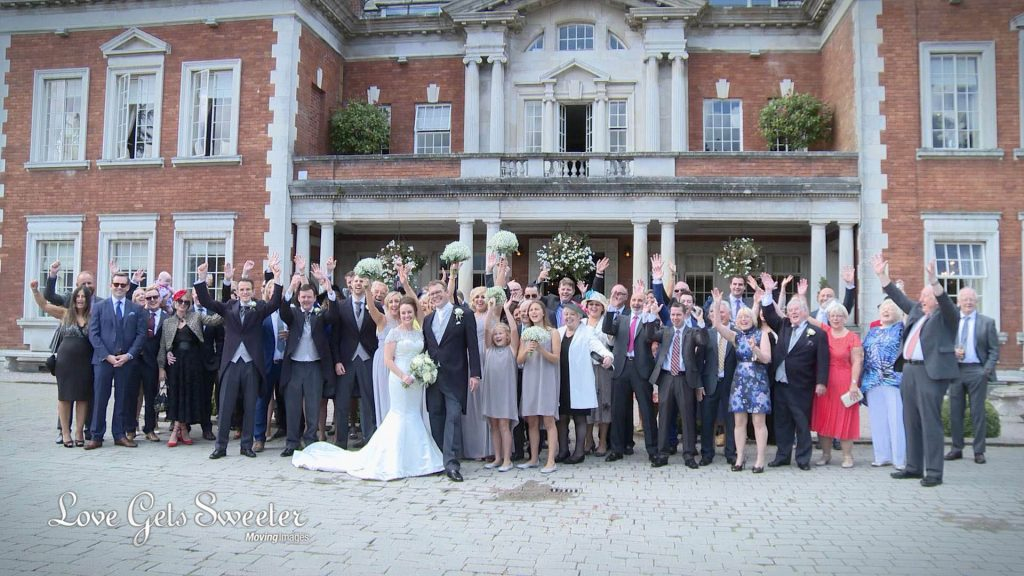 large group shot outside the front of Eaves Hall on wedding video