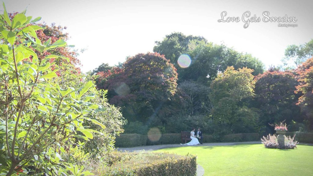 late afternoon sunshine bride and groom on bench in Eaves Hall gardens