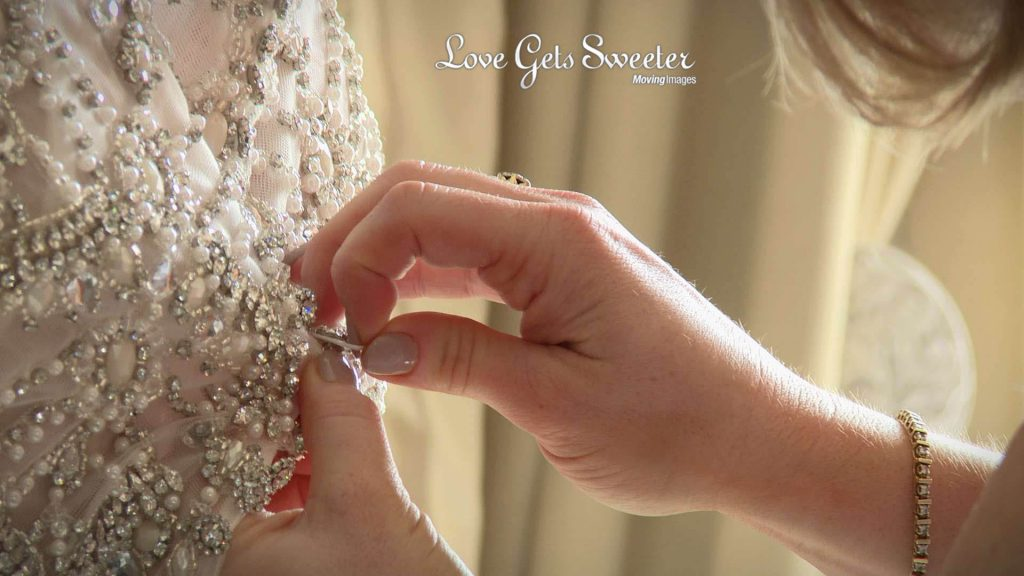 filming the bride get ready at Eaves Hall detail of back of wedding dress