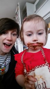 female videographer mum with daughter baking cakes and chocolate faces