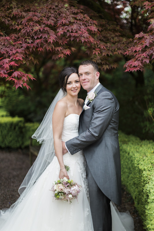 Lottie Designs at Eaves Hall with bride and groom in the garden with videographer