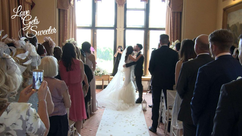 Their Cumbria wedding videographer films the moment the bride and groom enjoy a kiss after being announced as husband and wife at armathwaite hall in the lake district