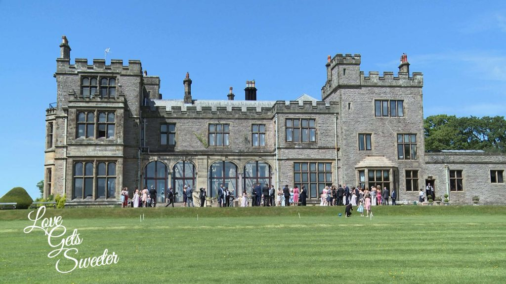 a wide shot of the stunning countryside lake district venue armathwaite hall with the wedding guests outside on the lawn