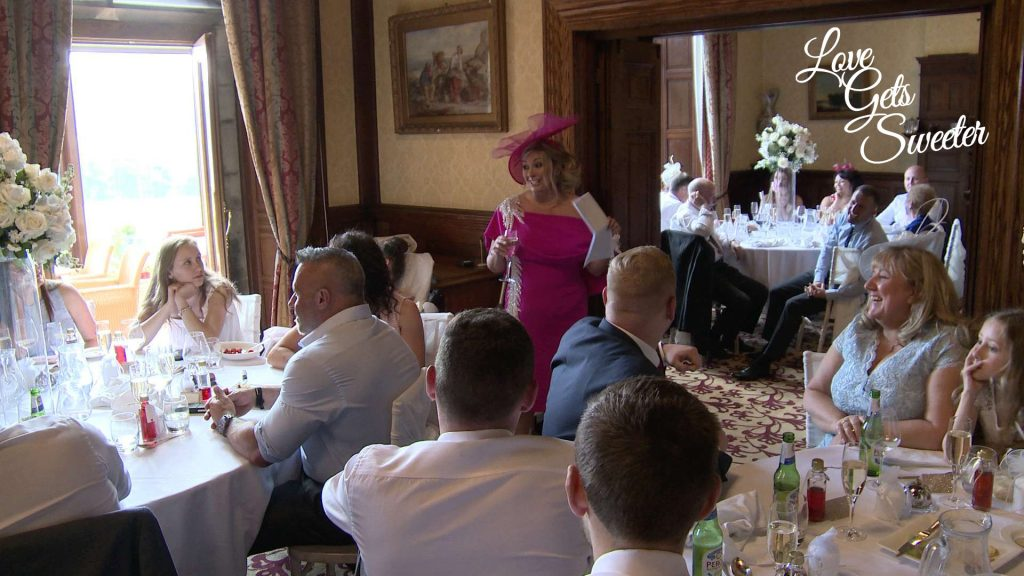 A still from their wedding video showing the wedding reception room with white and blush pink flowers during the mother of the bride speech at a wedding in armathwaite hall hotel in Keswick