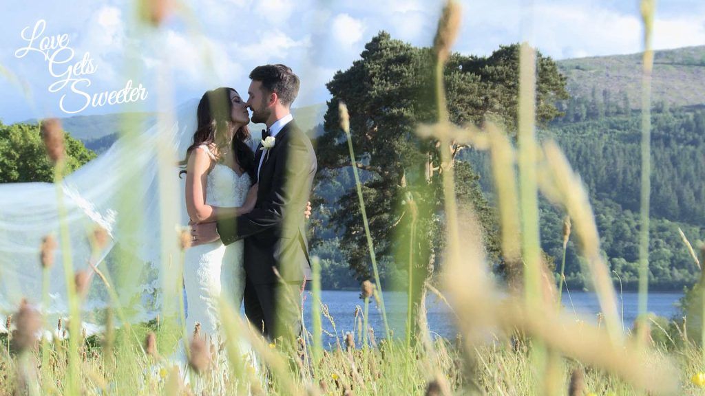bride and groom having a kiss in the field by Armathwaite Hall in front of Bassenthwaite Lake for their wedding videographer