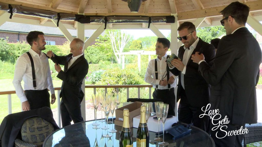 groom and ushers getting ready in the parents garden under the gazebo on a hot summers day in Penrith